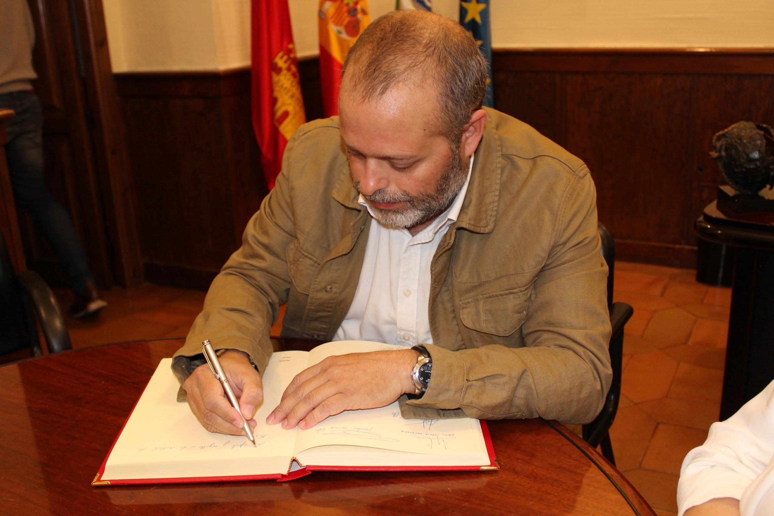 Rafael España firmando libro de honor