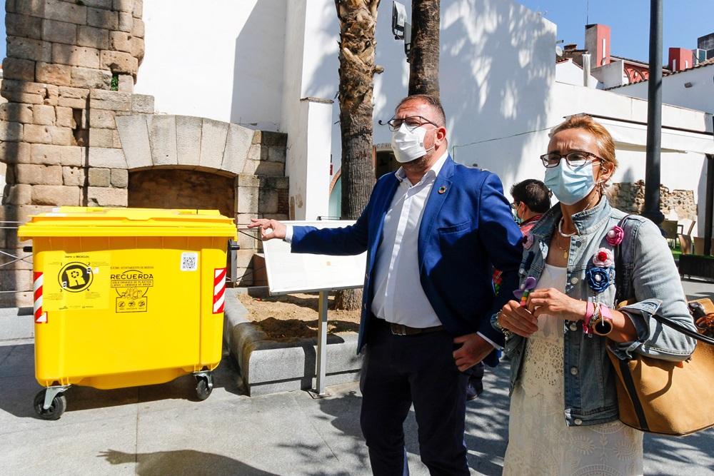 El alcalde y la delegada de limpieza muestran la imagen de los contenedores amarillos